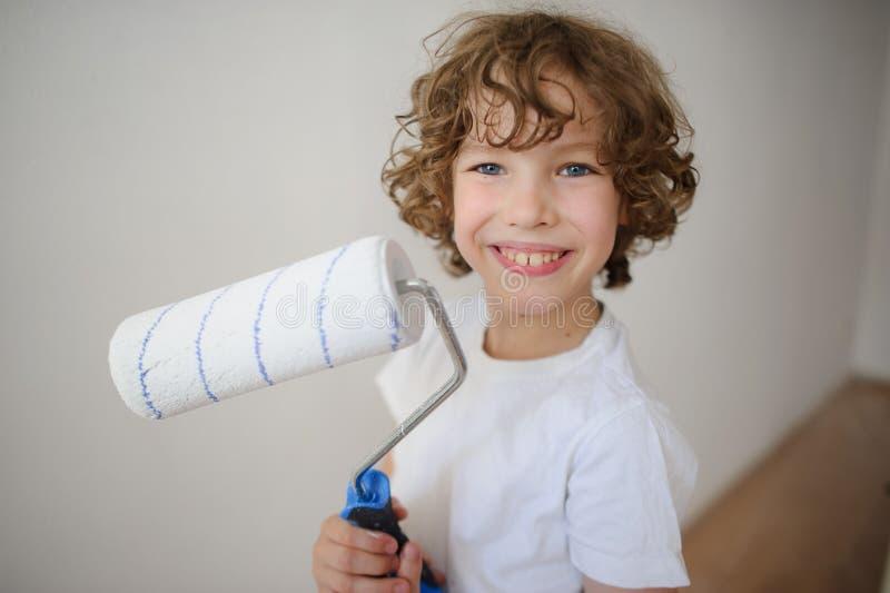 Vrolijke jongen met een rol aan verf in zijn handen royalty-vrije stock foto