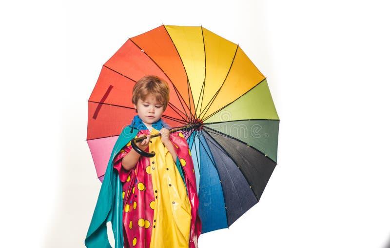 Vrolijke jongen in regenjas met kleurrijke paraplu De grootste kortingen voor alle de herfstkleren voor kinderen Regenende jonge  stock foto's