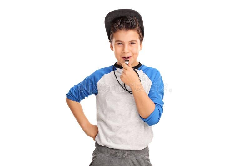 Vrolijke jongen in sportkleding die een fluitje blazen stock foto