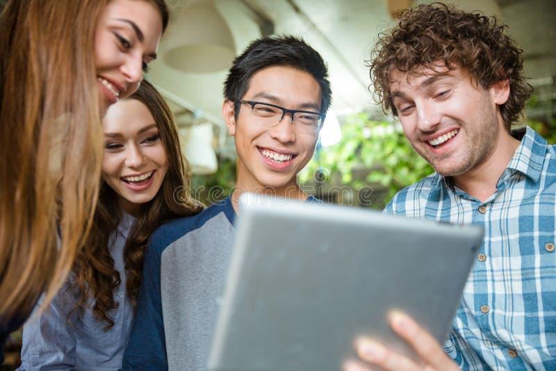 Vrolijke jongeren die en tablet gebruiken lachen royalty-vrije stock foto's