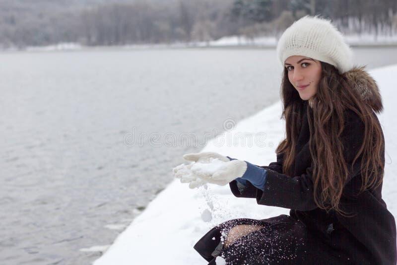 Vrolijke Kaukasische Jonge Vrouw in Sneeuwweer op de bank van t royalty-vrije stock foto's