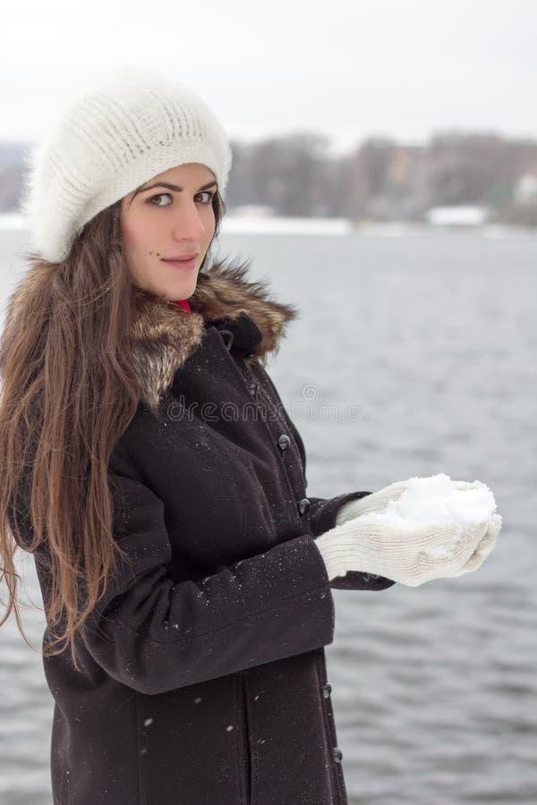 Vrolijke Kaukasische Jonge Vrouw in Sneeuwweer op de bank van t stock afbeeldingen