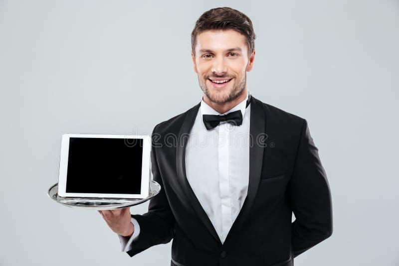 Vrolijke kelner in lege het schermtablet van de smokingholding op dienblad royalty-vrije stock foto's