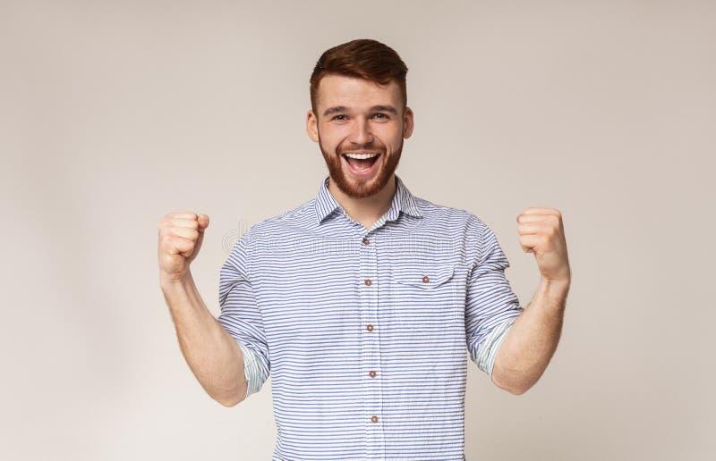 Vrolijke kerel die zijn bicepsen en het glimlachen tonen royalty-vrije stock foto's