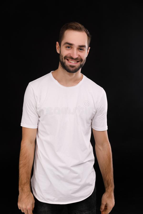 Vrolijke kerel in een witte T-shirt op een zwarte achtergrond royalty-vrije stock afbeelding