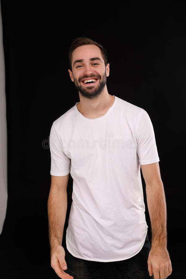 Vrolijke kerel in een witte T-shirt op een zwarte achtergrond stock fotografie