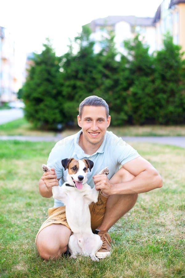 Vrolijke kerel op een gang in het park op een de zomerdag met zijn Jack Russell-hond Zij zijn volledig van vreugde, glimlachend,  royalty-vrije stock afbeeldingen