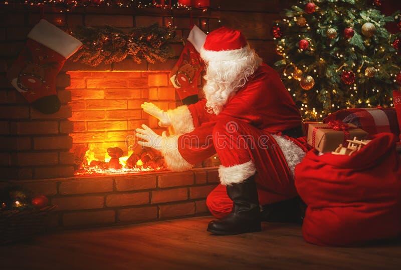 Vrolijke Kerstmis! de Kerstman dichtbij de open haard en boom met gi stock foto