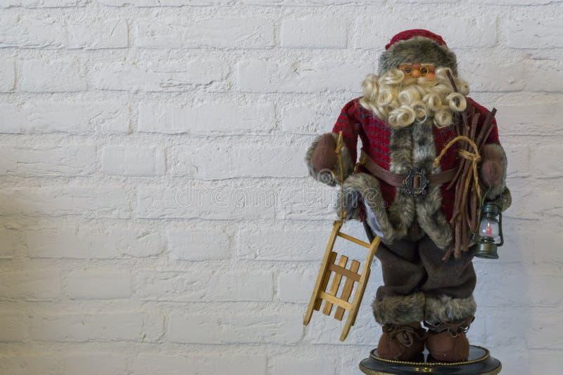 Vrolijke Kerstmis, de marionet van de Kerstman een ar en een lantaarn houden die op een witte bakstenen muurachtergrond wordt geï stock foto