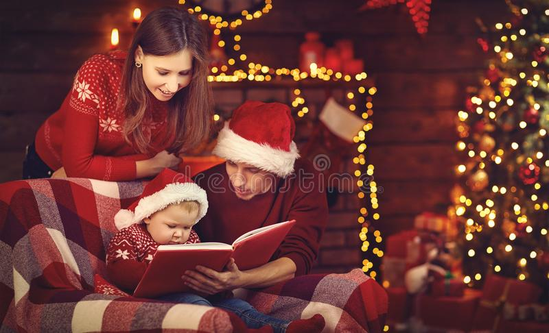 Vrolijke Kerstmis! de vader van de familiemoeder en baby gelezen boek dichtbij RT stock fotografie