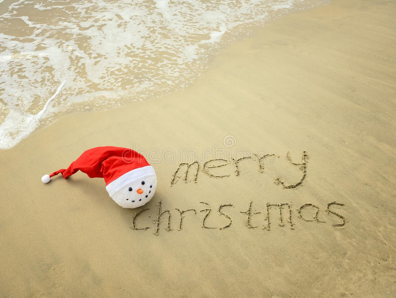 Vrolijke Kerstmis die op tropisch strand wit zand wordt geschreven met sneeuwman stock foto