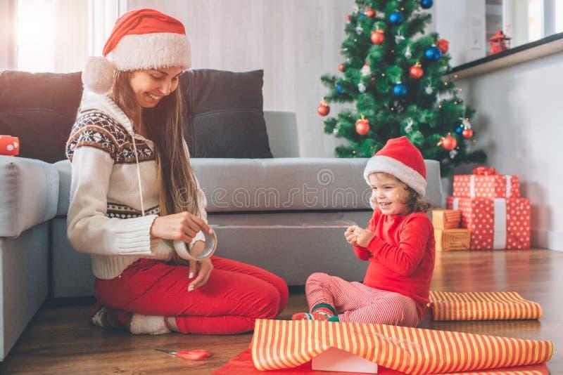 Vrolijke Kerstmis en de Gelukkige Nieuwjaar Positieve en speelse jonge vrouw en het meisje zitten op vloer Zij glimlachen en lach royalty-vrije stock fotografie
