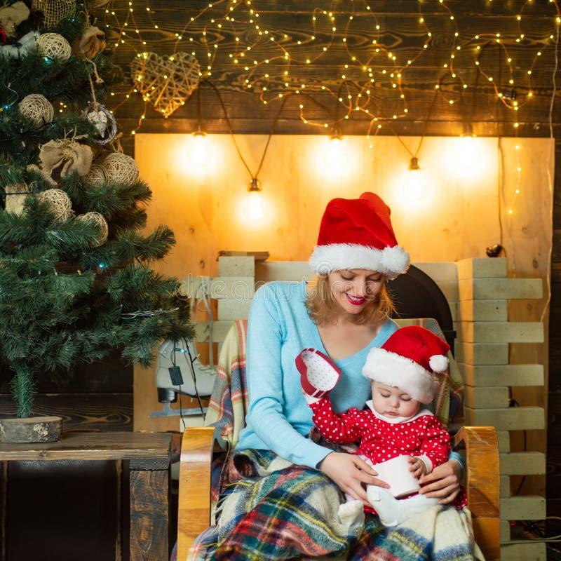 Vrolijke Kerstmis en Gelukkig Nieuwjaar Het mamma en de dochter verfraaien de Kerstboom Kerstmis houdende van familie stock afbeeldingen