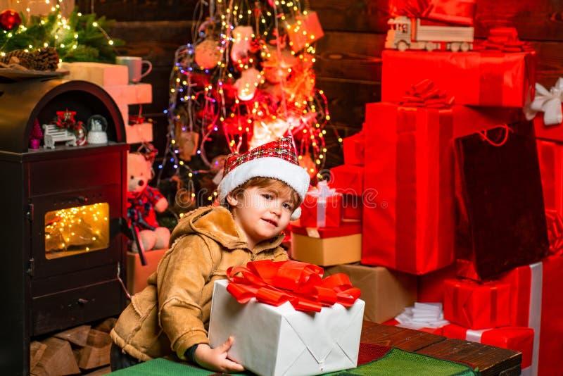 Vrolijke Kerstmis en Gelukkig Nieuwjaar Leuk weinig spel van de kindjongen dichtbij Kerstmisboom Het jonge geitje geniet thuis de royalty-vrije stock foto's