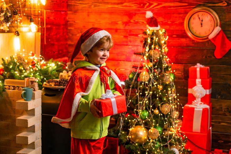 Vrolijke Kerstmis en Gelukkig Nieuwjaar Leuk weinig spel van de kindjongen dichtbij Kerstmisboom Het jonge geitje geniet thuis de stock foto