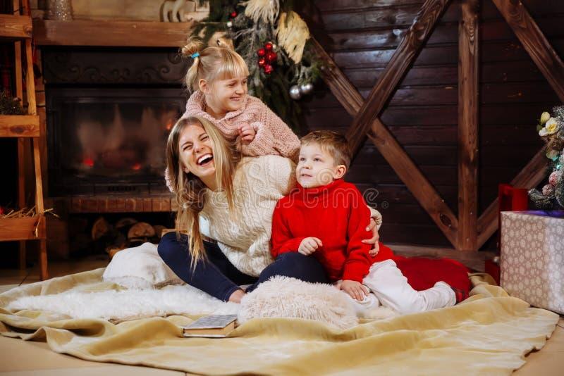 Vrolijke Kerstmis en Gelukkig Nieuwjaar Momandkinderen die pret hebben dichtbij Kerstboom binnen dichtbij Kerstboom royalty-vrije stock afbeelding
