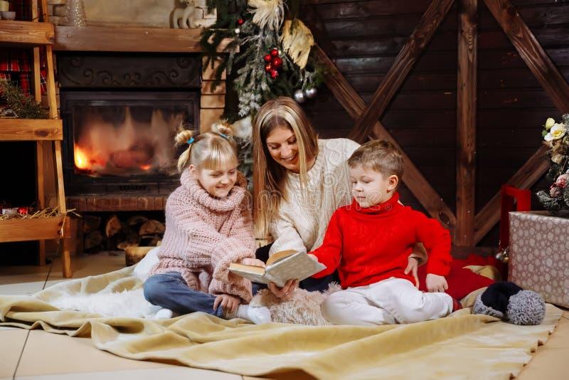 Vrolijke Kerstmis en Gelukkig Nieuwjaar Mooie familie in Kerstmisbinnenland Vrij jonge moeder die een boek lezen aan haar royalty-vrije stock foto's