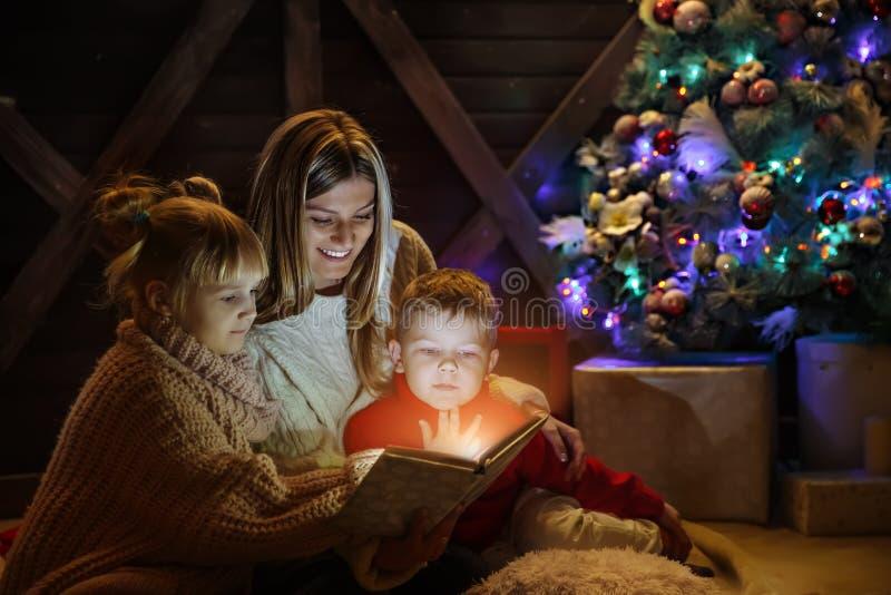 Vrolijke Kerstmis en Gelukkig Nieuwjaar Mooie familie in Kerstmisbinnenland Vrij jonge moeder die een boek lezen aan haar stock foto's