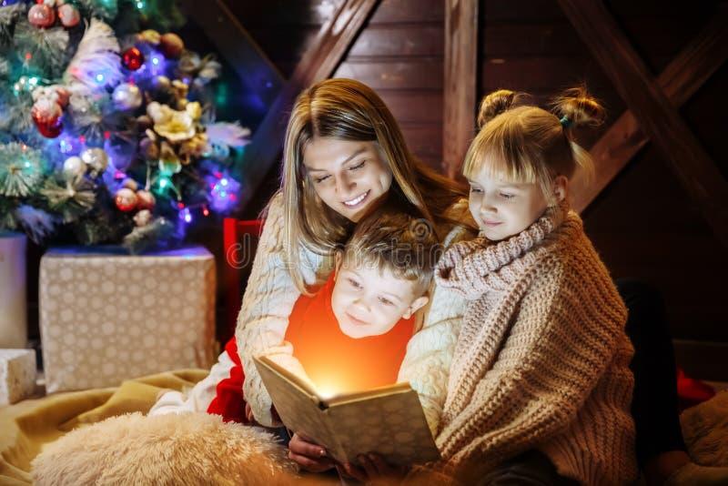 Vrolijke Kerstmis en Gelukkig Nieuwjaar Mooie familie in Kerstmisbinnenland Vrij jonge moeder die een boek lezen aan haar royalty-vrije stock afbeelding