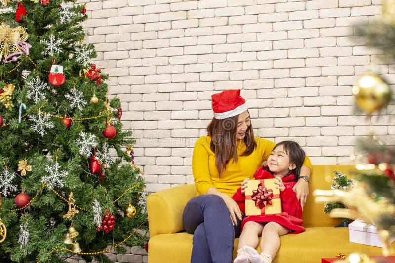Vrolijke Kerstmis en Gelukkig Vakantie of Gelukkige Nieuw jaar Het mamma geeft giften aan kinderen Het leuke meisje geeft zijn ge royalty-vrije stock afbeeldingen