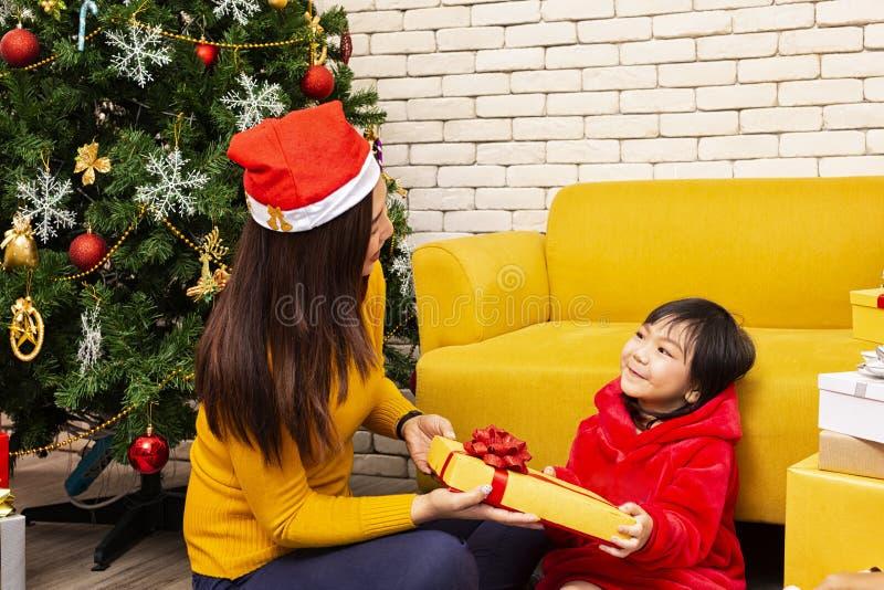 Vrolijke Kerstmis en Gelukkig Vakantie of Gelukkige Nieuw jaar Het mamma geeft giften aan kinderen Het leuke meisje geeft zijn ge royalty-vrije stock foto