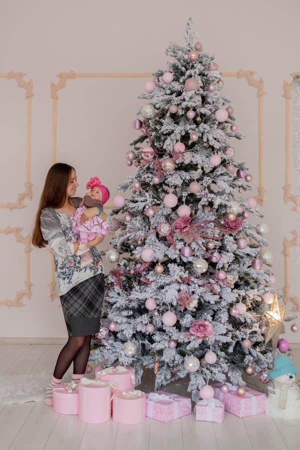 Vrolijke Kerstmis en Gelukkig Vakantie vrij jong mamma die een boek binnen lezen aan haar leuke dochter dichtbij Kerstboom stock afbeelding