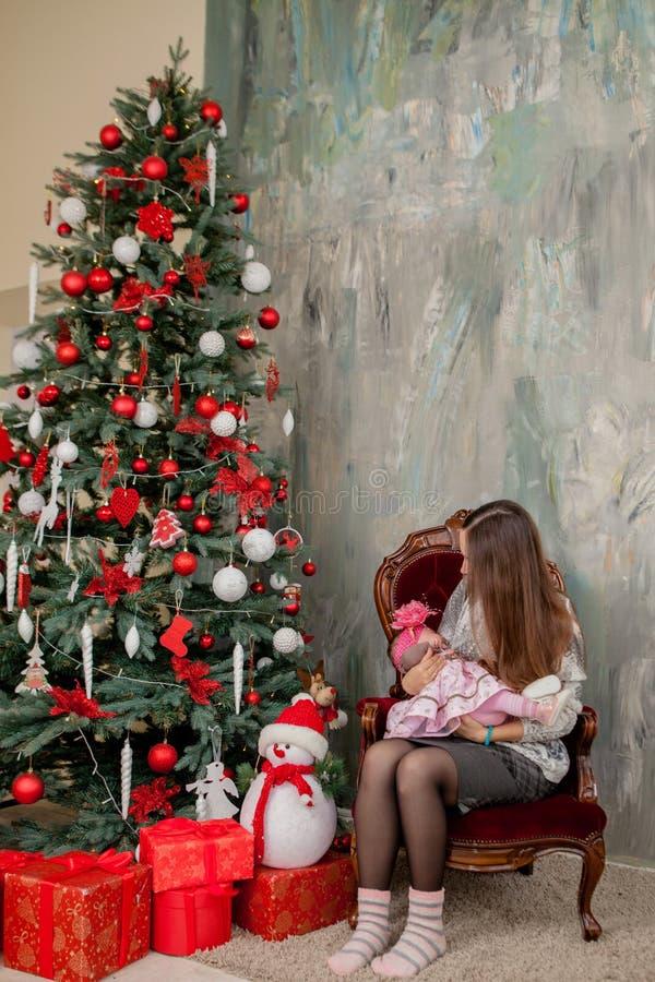 Vrolijke Kerstmis en Gelukkig Vakantie vrij jong mamma die een boek binnen lezen aan haar leuke dochter dichtbij Kerstboom stock fotografie