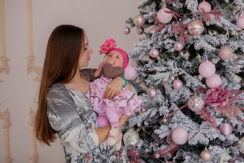 Vrolijke Kerstmis en Gelukkig Vakantie vrij jong mamma die een boek binnen lezen aan haar leuke dochter dichtbij Kerstboom royalty-vrije stock afbeelding
