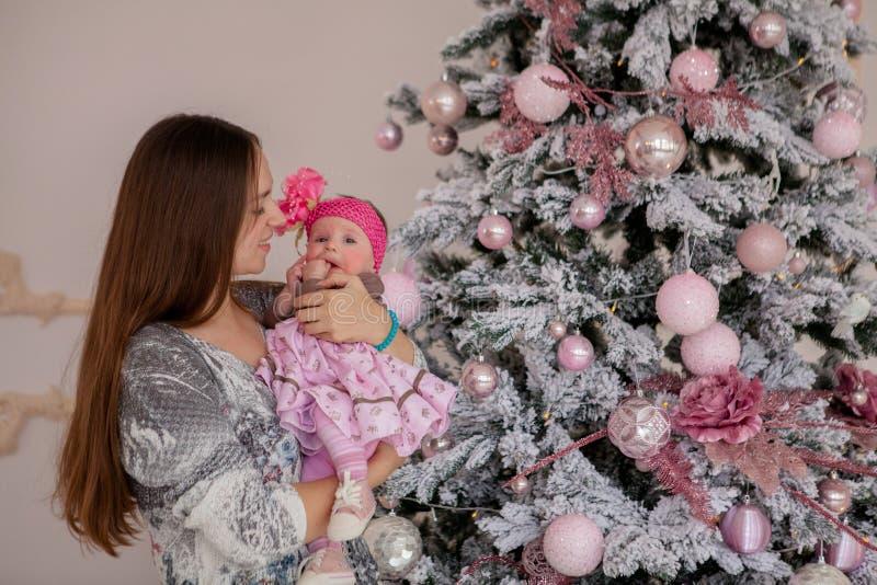Vrolijke Kerstmis en Gelukkig Vakantie vrij jong mamma die een boek binnen lezen aan haar leuke dochter dichtbij Kerstboom stock foto