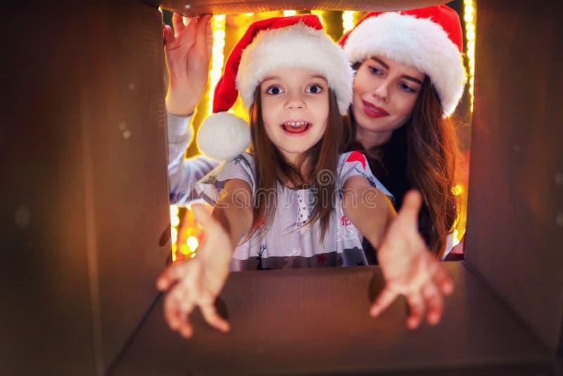 Vrolijke Kerstmis en Gelukkig Vakantie Vrolijk mamma en haar leuk dochtermeisje die aanwezige Kerstmis openen Ouder en royalty-vrije stock foto's