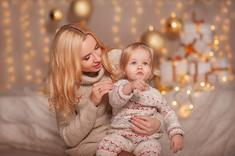 Vrolijke Kerstmis en Gelukkige vakantie! Klein jong geitjemeisje met mammazitting in verfraaide ruimte met giften en lichten en h stock afbeeldingen