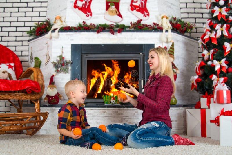 Vrolijke Kerstmis en Gelukkige Vakantie! Mamma en zoons het spelen dichtbij de open haard, eet mandarijnen royalty-vrije stock afbeelding