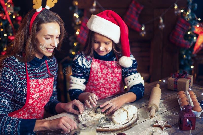 Vrolijke Kerstmis en gelukkige vakantie Moeder en dochter kokende Kerstmiskoekjes stock foto