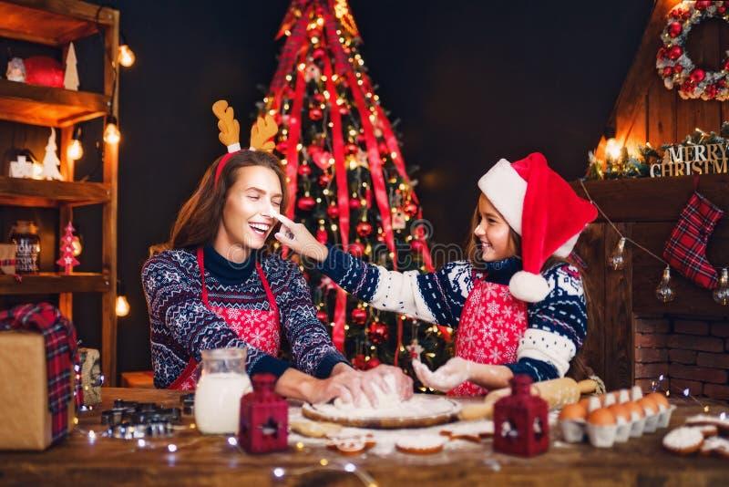 Vrolijke Kerstmis en gelukkige vakantie Moeder en dochter kokende Kerstmiskoekjes stock afbeeldingen