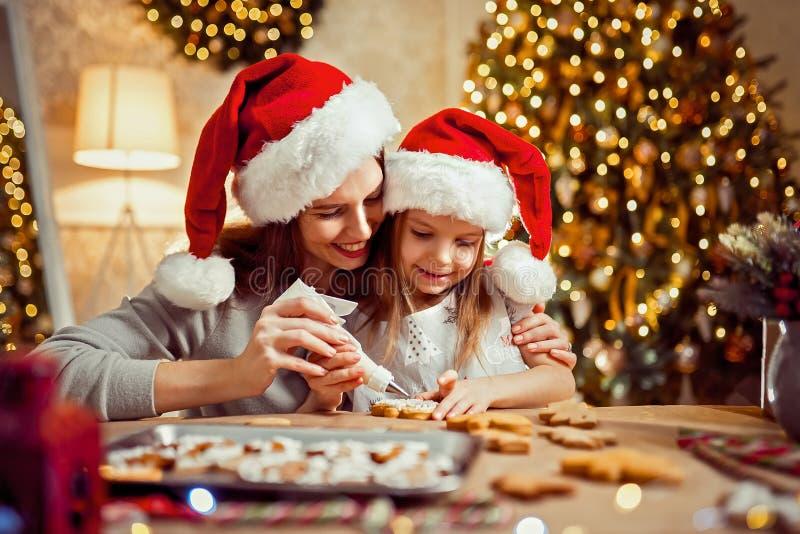 Vrolijke Kerstmis en gelukkige vakantie Moeder en dochter kokende Kerstmiskoekjes stock foto's
