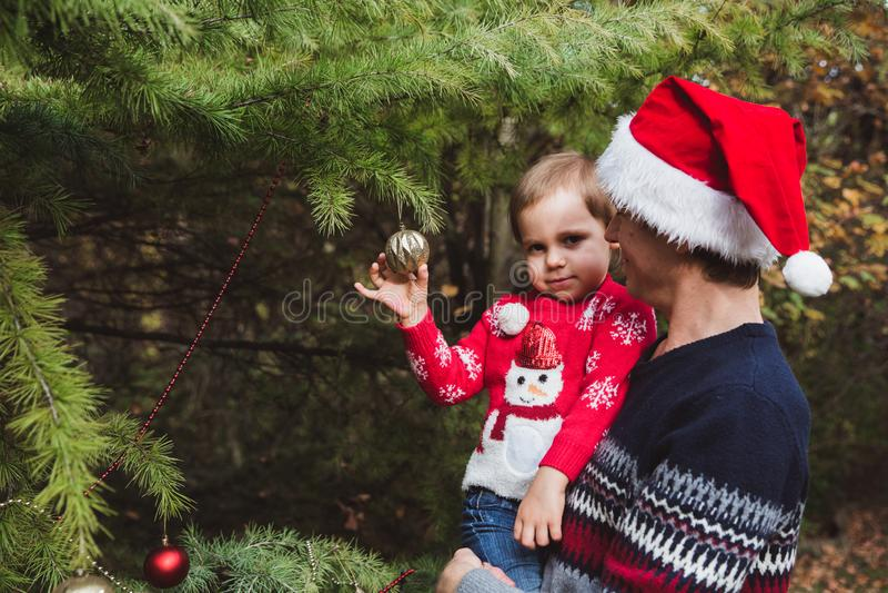 Vrolijke Kerstmis en gelukkige vakantie Vader in rode Kerstmishoed en dochter die in rode sweater de Kerstboom verfraaien openluc stock fotografie