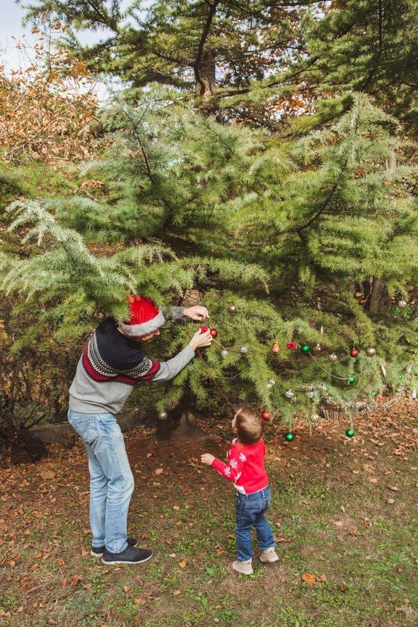 Vrolijke Kerstmis en gelukkige vakantie Vader in rode Kerstmishoed en dochter die in rode sweater Kerstmis verfraaien royalty-vrije stock fotografie