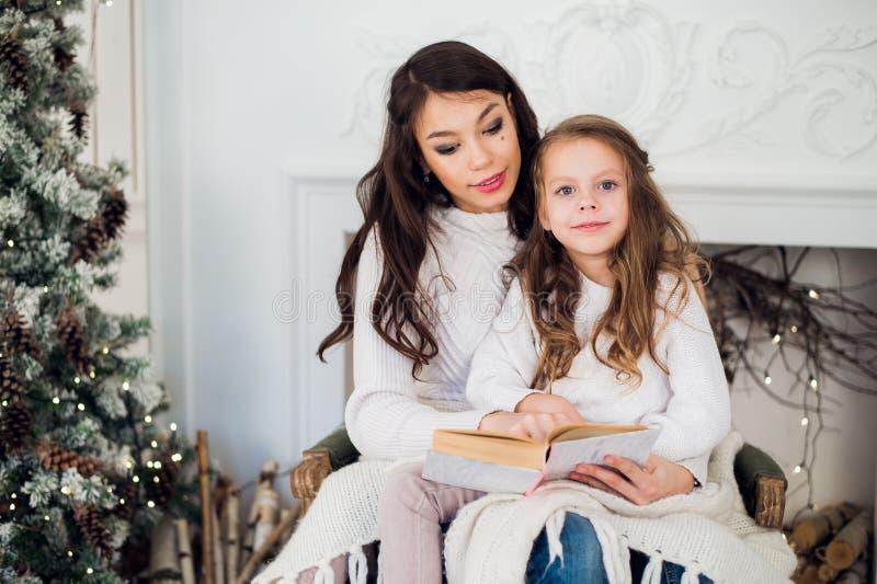 Vrolijke Kerstmis en Gelukkige Vakantie, vrij jong mamma die een boek binnen lezen aan haar leuke dochter dichtbij boom stock afbeeldingen