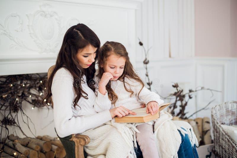 Vrolijke Kerstmis en Gelukkige Vakantie, vrij jong mamma die een boek binnen lezen aan haar leuke dochter dichtbij boom stock foto's