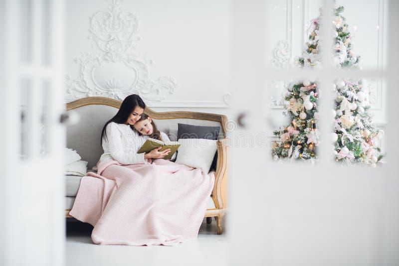 Vrolijke Kerstmis en gelukkige vakantie Vrij jong mamma die een boek binnen lezen aan haar leuke dochter dichtbij Kerstboom royalty-vrije stock foto's