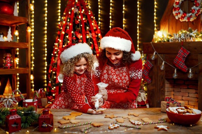 Vrolijke Kerstmis en gelukkige vakantie Vrolijk leuk krullend meisje en haar oudere zuster in santashoeden het koken stock fotografie