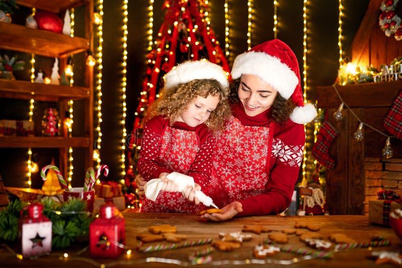 Vrolijke Kerstmis en gelukkige vakantie Vrolijk leuk krullend meisje en haar oudere zuster in santashoeden het koken royalty-vrije stock afbeeldingen