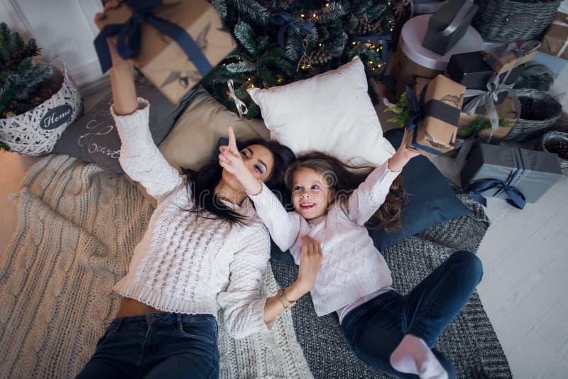 Vrolijke Kerstmis en gelukkige vakantie Vrolijk mamma en haar leuk dochtermeisje die giften ruilen Ouder en weinig kind stock foto