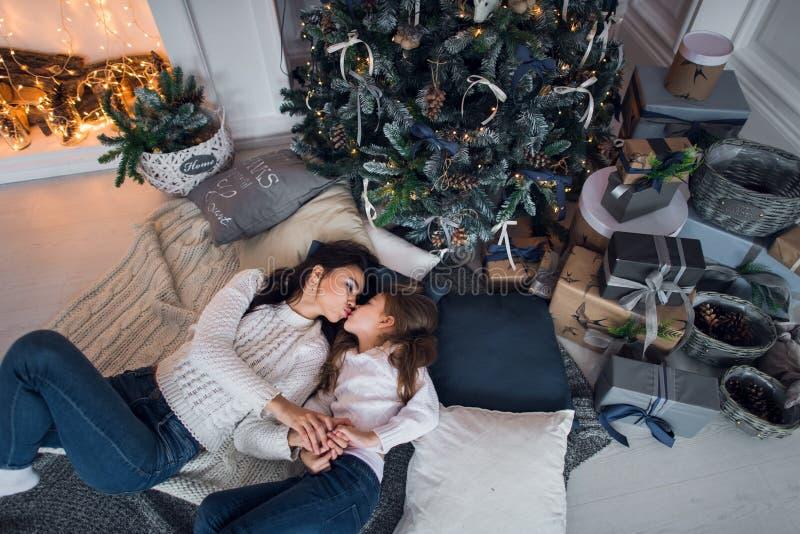 Vrolijke Kerstmis en gelukkige vakantie Vrolijk mamma en haar leuk dochtermeisje die giften ruilen Ouder en weinig kind royalty-vrije stock foto's