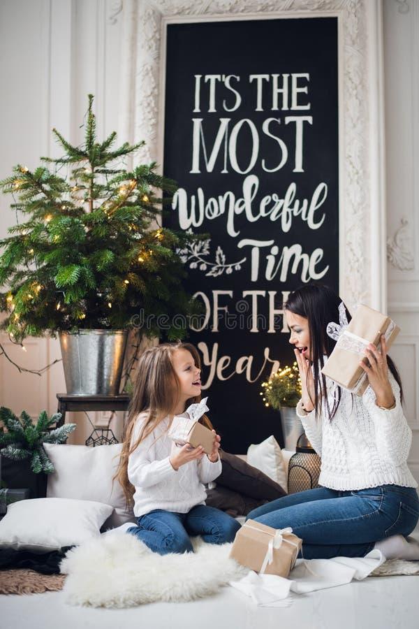 Vrolijke Kerstmis en gelukkige vakantie Vrolijk mamma en haar leuk dochtermeisje die giften ruilen Ouder en weinig kind stock foto's