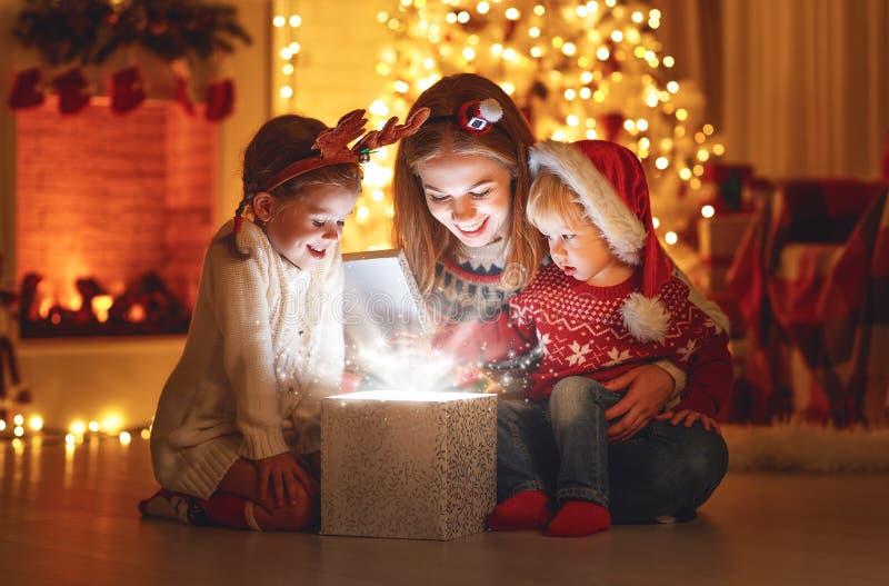 Vrolijke Kerstmis! familiemoeder en kinderen met magische gift bij stock afbeelding