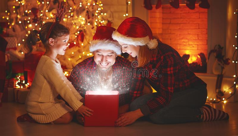 Vrolijke Kerstmis! het de gelukkige vader en kind van de familiemoeder met magisch stock fotografie