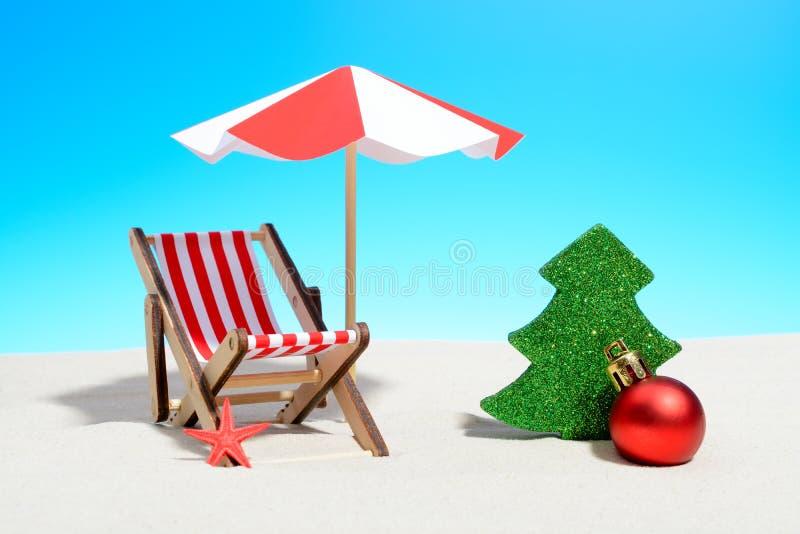 Vrolijke Kerstmis op strandconcept Zitkamerstoel met paraplu en Kerstmisdecoratie royalty-vrije stock afbeeldingen