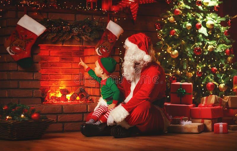 Vrolijke Kerstmis! Santa Claus en weinig elf dichtbij open haard royalty-vrije stock foto's