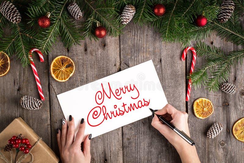 Vrolijke Kerstmishand het van letters voorzien inschrijving op oude houten achtergrond Van pijnboomtakken en kegels kader Nieuwe  stock afbeelding